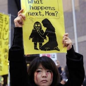 """Mulher segura placa onde uma criança pergunta """"O que acontece depois, mamãe?"""", em protesto na sede da Tepco, em dezembro"""