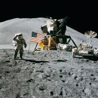 A public domain photo of Apollo 15 on the Moon's surface, with the flag flying and a saluting astronaut. The Moon Lander and Moon Rover to the right.