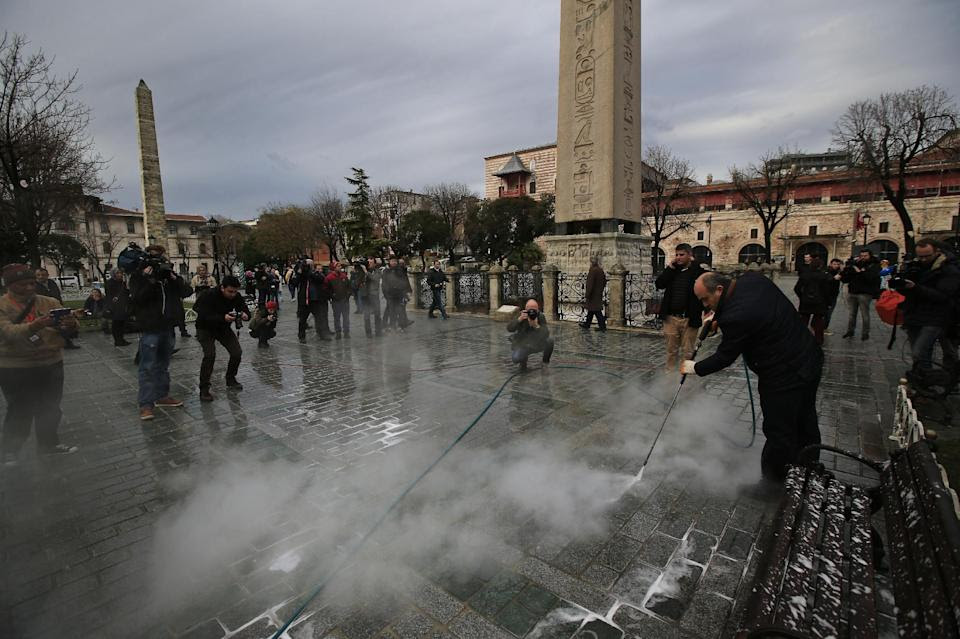 A municipality worker cleans the pavement at the site of Tuesday's explosion in the historic Sultanahmet district in Istanbul, Wednesday, Jan. 13,...