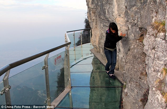 Don't look down: A brave tourist walks along the glass path that was built of the side of a cliff 1430m above sea level on Tianmen Mountain in Zhangjiajie, China