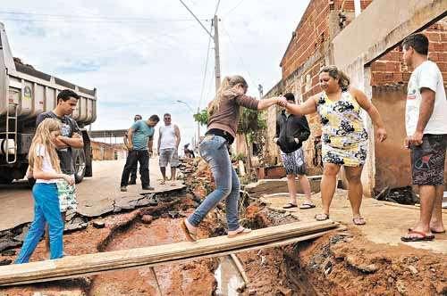 Moradores se arriscam para chegar em casa no Condomínio Por do Sol: chuva provocou erosão e inundou três residências (Marcelo Ferreira/CB/D.A Press)