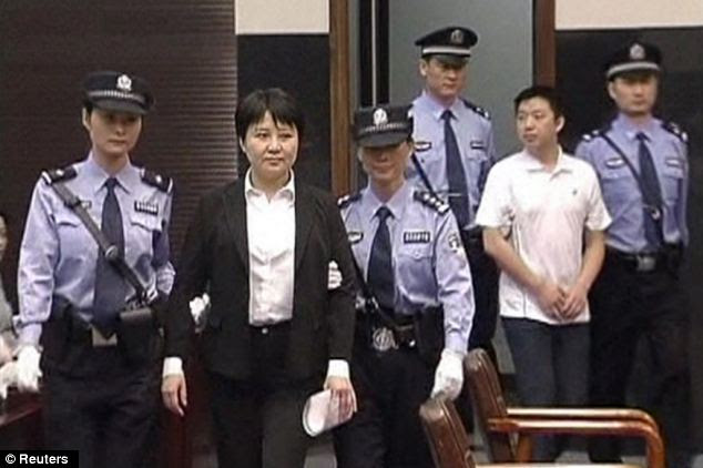 Facing trial: Gu Kailai, 52, and aide Zhang Xiaojun, 33, are escorted into the Hefei City People's Court to face charges relating to the murder of British businessman Neil Heywood