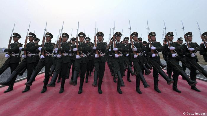 TO GO WITH STORY China-politics-60years-military BY DAN MARTIN In a picture taken on September 25, 2009 Chinese honour guards applaud their comrades as they rehearse for the National Day parade in Beijing . The People's Liberation Army marched into Beijing in 1949 as a ragtag peasant force, but this week it will show what a difference six decades and billions of dollars in funding can make. CHINA OUT AFP PHOTO (Photo credit should read AFP/AFP/Getty Images)