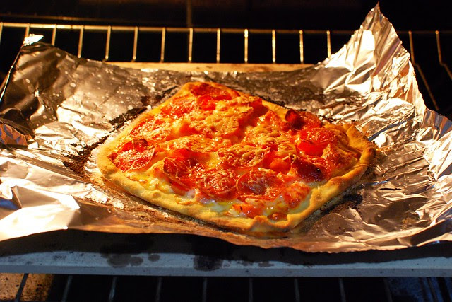 Homemade pizza baking in an oven.