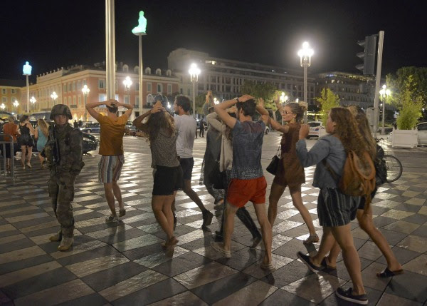 Image: People cross the street with their hands on thier heads as a French soldier secures the area after at least 60 people were killed in Nice when a truck ran into a crowd celebrating the Bastille Day national holiday