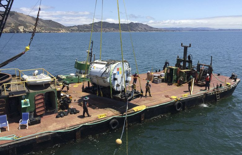"""A Microsoft prototype underwater data center — affectionately dubbed the """"Leona Philpot"""" after a video-game character, is shown on a barge before being lowered into the Pacific Ocean off central California in August. (MICROSOFT/NYT)"""