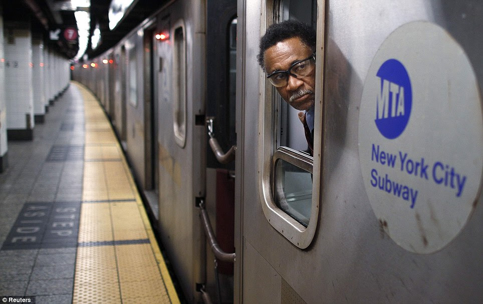 Final check: A subway worker, on the last northbound 4 train, looks down the track to safely close the doors at Grand Central station in New York on Sunday