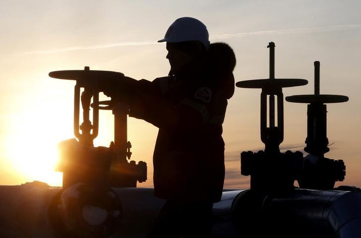 FILE PHOTO: A worker checks the valve of an oil pipe at the Lukoil company owned Imilorskoye oil field outside the Siberian city of Kogalym, Russia, January 25, 2016.    REUTERS/Sergei Karpukhin/File Photo