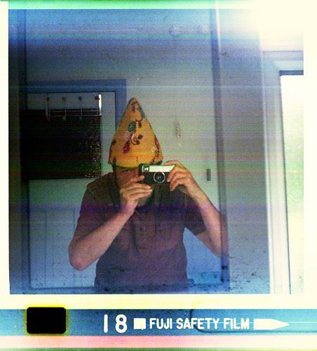 reflected self-portrait with Kodak Instamatic 233 camera and narrow yellow hat by pho-Tony