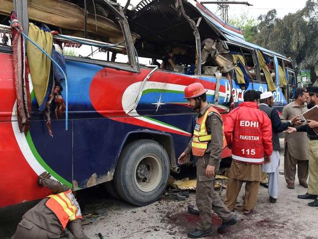 Voluntários paquistaneses e forças de segurança inspecionam ônibus destruído (Foto: AFP Photo)