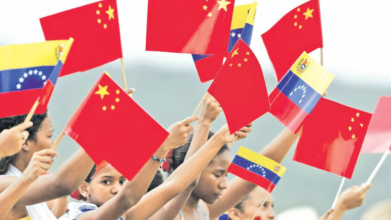Venezuelan students waving Chinese and Venezuelan flags.