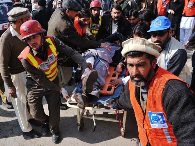Equipes de resgate carregam ferido em ataque a universidade no Paquistão nesta quarta-feira (20) (Foto: Hasham Ahmed/AFP)
