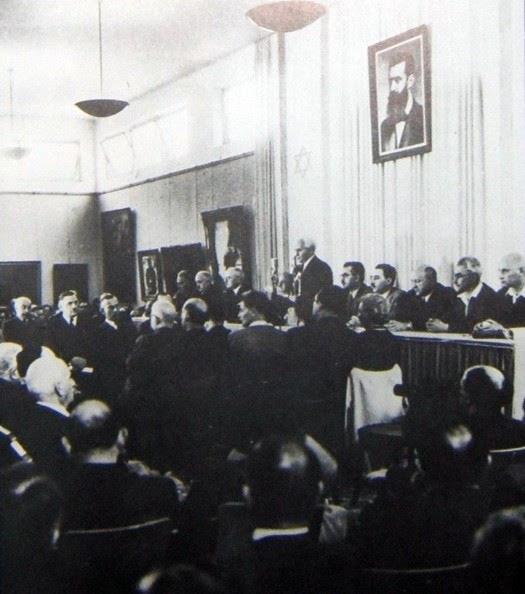 La dichiarazione di indipendenza di David Ben-Gurion. Alle spalle, la foto di Theodor Herzl e la bandiera del nuovo Stato d'Israele.