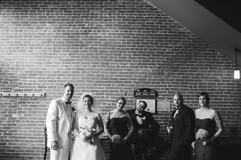 The Bride and Groom hang out with their wedding party and have a beer at Carlyle Brewing Company following their wedding at Court Street United Methodist Church in downtown Rockford Illinois for an Autumn wedding.