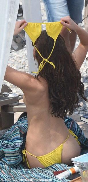 Desafiando a nu: A beleza morena tirou o top do biquíni amarelo brilhante para o momento romântico