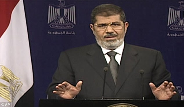 Mohammed Morsi, who a year ago was inaugurated as Egypt's first freely elected president, pledged to protect his 'constitutional legitimacy' with his life in an emotional televised speech
