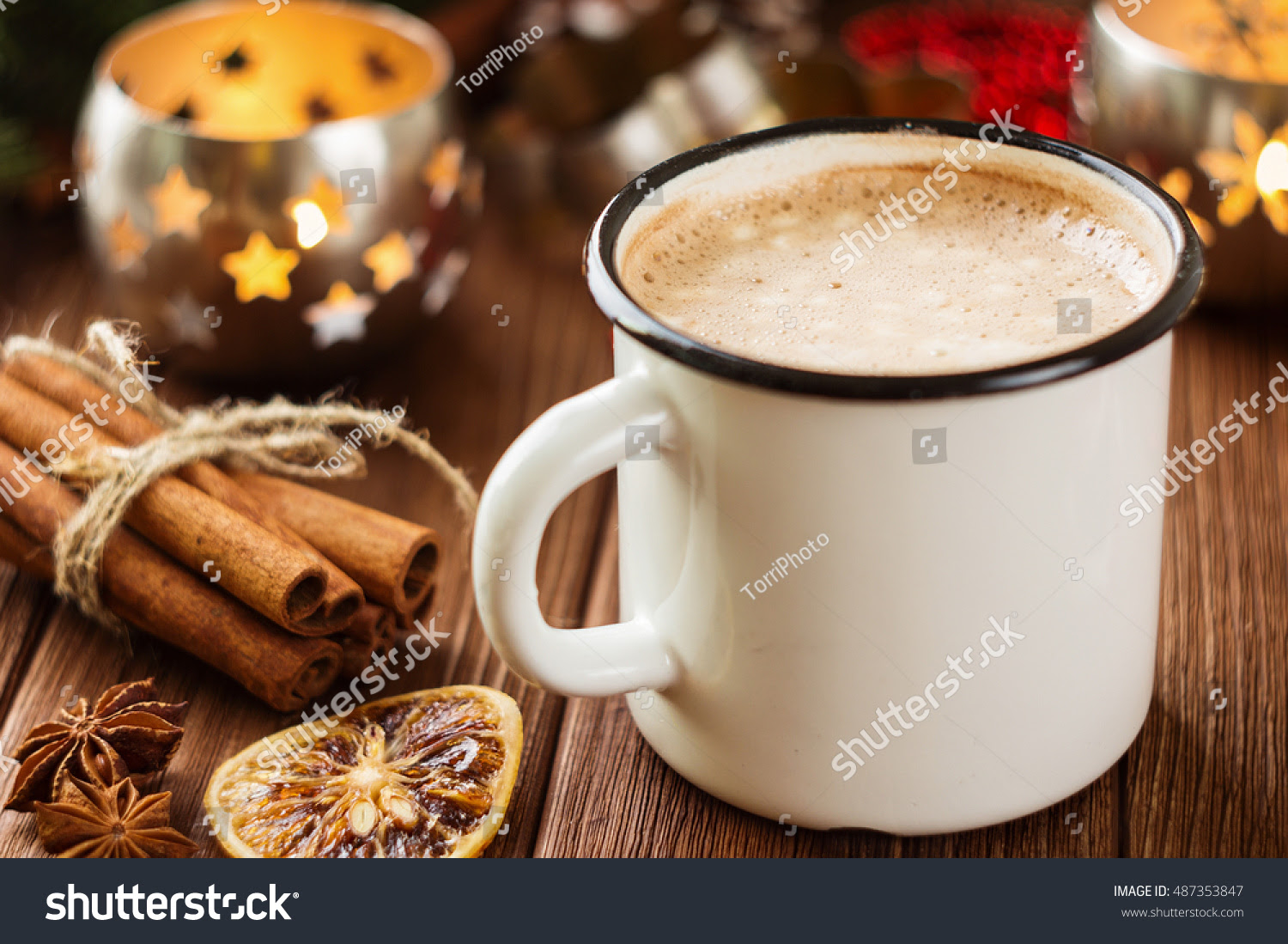 Enamel cup of hot cocoa with mini marshmallows on rustic background with christmas decorations