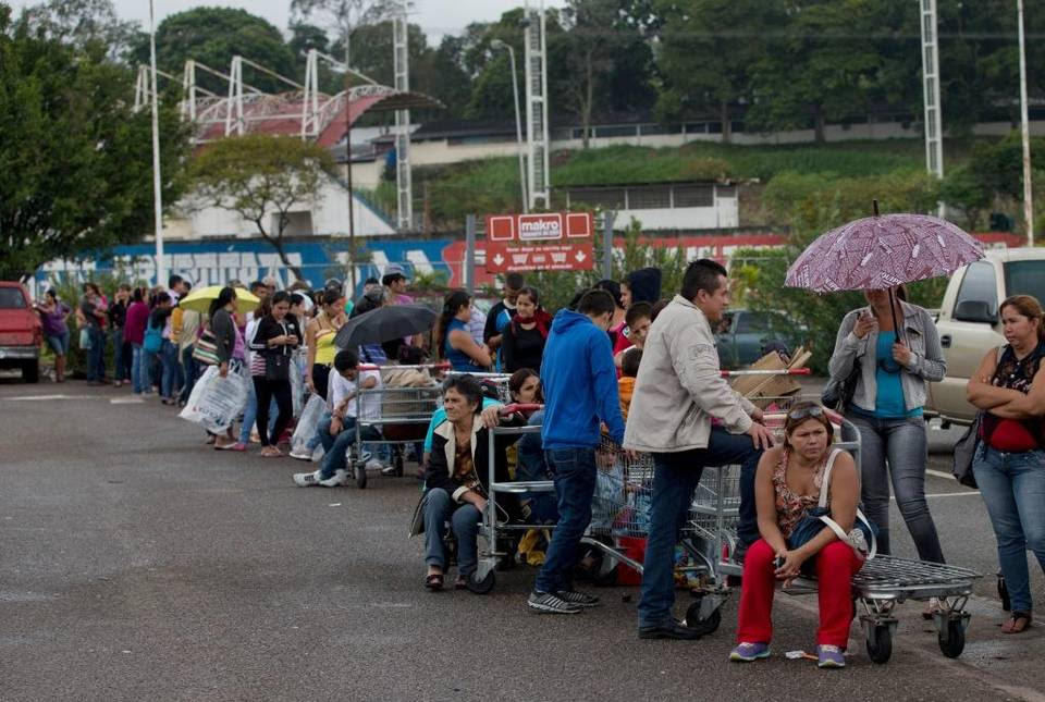 Patrons line up on a supermarket parking lot in San Cristobal, Venezuela, in January.