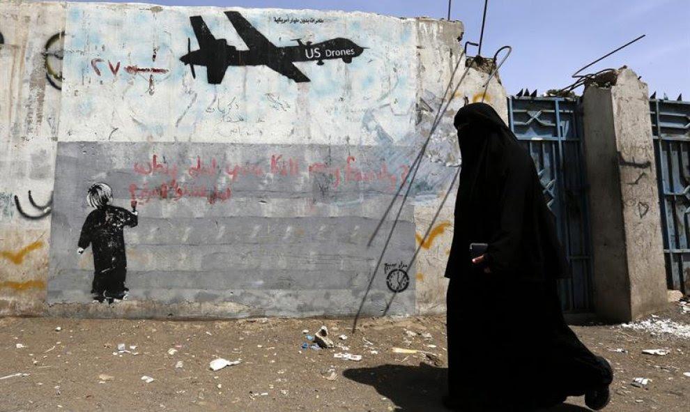 Una mujer camina junto a unas pintadas en contra de los drones estadounidenses y los ataques de Estados Unidos contra supuestas pociones de Al-Qaeda en Saná, Yemen. EFE/Yahya Arhab
