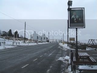 road,pub sign,snow,hotel,moors,slush