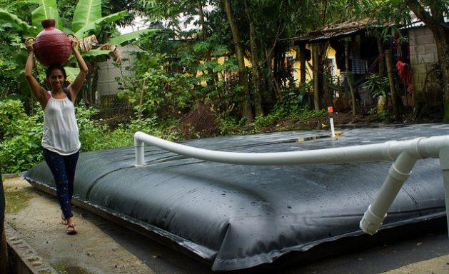 Corina Canjura carga un cántaro de agua que acaba de llenar, gracias a un sistema de captación de agua lluvia localizado en el terreno al lado de su vivienda, que además abastece a otras 12 familias del caserío de Los Corvera, en el municipio de Tepetitán, en el departamento de San Vicente, en el centro de El Salvador. Crédito: Edgardo Ayala/IPS