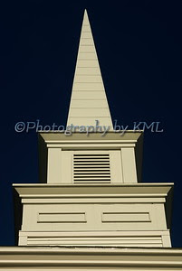 a white church steeple against a dark blue sky