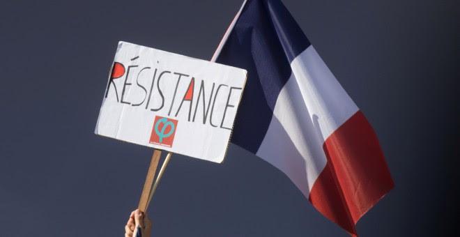 Un manifestante tiene una bandera francesa y un logo de la Francia Insumisa que dice: 'Resistencia'. REUTERS / Philippe Wojazer