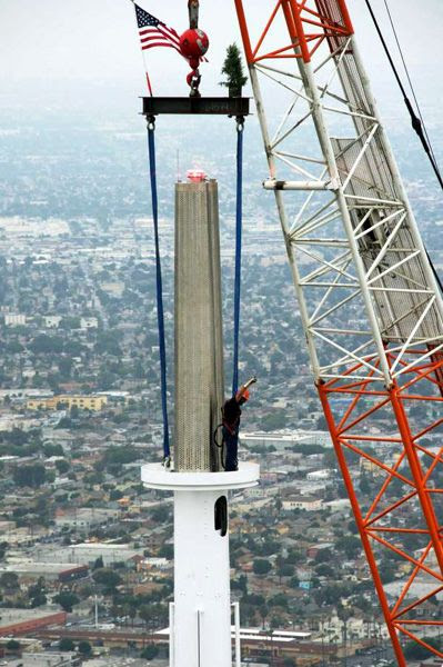A construction worker stands on the final spire segment as it was being installed atop the Wilshire Grand Center on September 3, 2016.