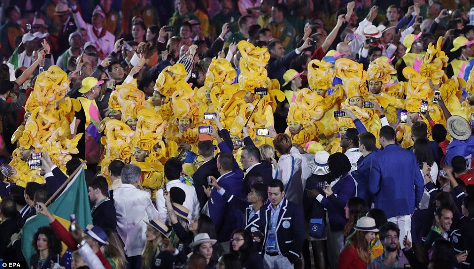 Dançarinos posar para fotos como atletas tirar fotos deles durante a cerimônia de abertura dos Jogos Olímpicos de 2016 no Rio de Janeiro, Brasil