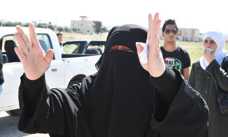 A Syrian woman gestures at the Jordanian border