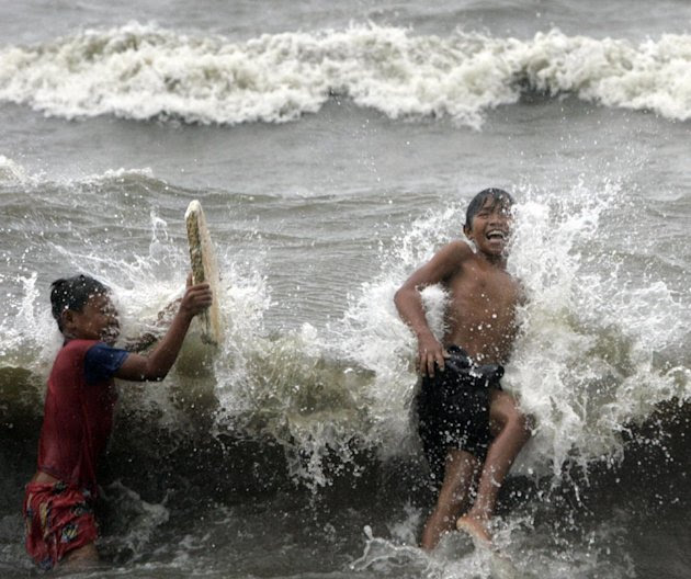 Two boys enjoy the surf due to Typhoon Nanmadol Saturday, Aug. 27, 2011 in Manila, Philippines. Forecasters said the typhoon hit the northeastern tip of the country with 121 miles (195 kilometers) per