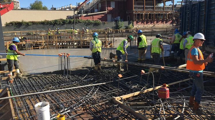 Construction crews are pouring the concrete atop the seven-level, below-grade parking garage at One Uptown.