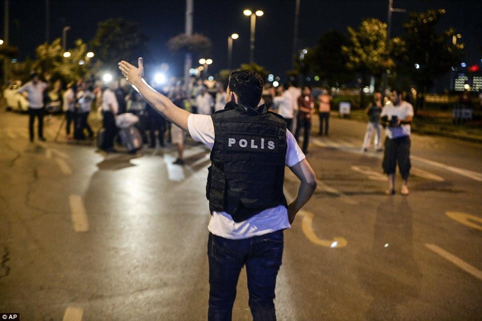 Um policial orienta turistas aterrorizados e outras pessoas presentes no aeroporto turco após o ataque fatal que matou dezenas de pessoas