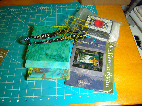 """prize #1 included 20 light aqua hoffman batik 6"""" squares,  20 dark aqua hoffman batik 6"""" squares, a McKenna Ryan pattern and the other things in the photo."""