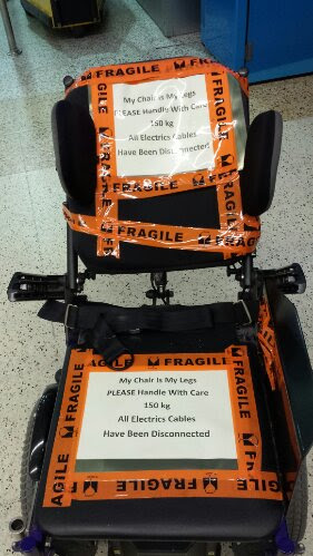 image showing John's wheelchair with orange fragile tape, and 2 signs saying 'My chair is my legs, please handle with care. 150kg all electrics cables have been disconnected'
