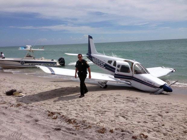 Equipes de emergência são vistas ao lado de avião que caiu em praia da Flórida neste domingo (27), matando um homem e ferindo sua filha de 9 anos. Ambos estavam na areia e foram atingidos pela aeronave (Foto: Sarasota County Sheriff's Office/AP)