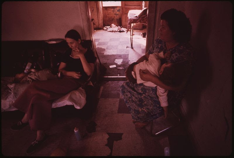 File:MRS. MAY WATKINS (RIGHT) SITS IN HER MULKY SQUARE HOUSE WITH THE YOUNGEST OF HER NINE CHILDREN AND A DAUGHTER-IN-LAW.... - NARA - 553544.jpg
