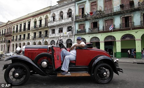 A man sits in an old car as he waits for tourists in Havana yesterday. Mr Obama's new policies are expected to usher in a new era of openness between Cuba and the U.S.