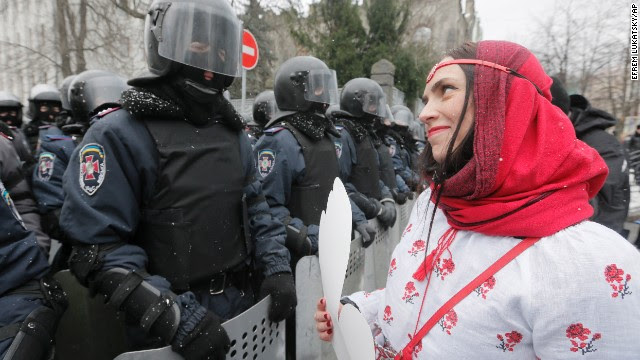 A pro-European Union activist holds a cut-out paper heart as she faces police at the presidential office in Kiev, Ukraine, on December 8.