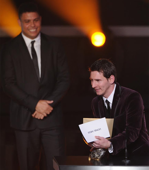 Messi holding the trophy with Ronaldo smiling behind him at FIFA Balon d'Or 2011