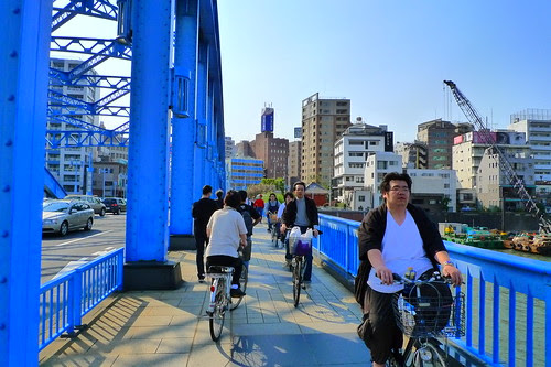 People cycling past one of the many Sumida River bridges