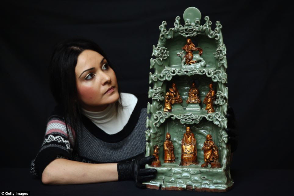 A British Museum employee poses behind a 15th century 'Longquan Shrine'