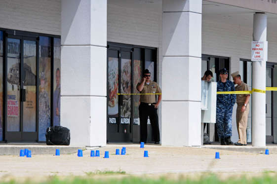 Reserve Recruitment personnel stand outside a Navy recruiting building as the area is cordoned off with blue shell casing markers in the parking lot on Thursday, July 16, 2015 in Chattanooga, Tenn.  At least two military facilities in Tennessee were attacked in shootings Thursday, including one at a Navy recruiting building, officials said.