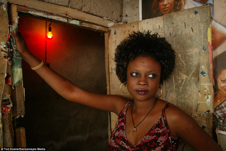 A woman stands in a doorway in the Badia district in Lagos