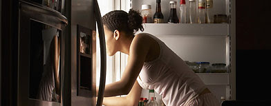 Young woman looking in refrigerator, night, side view IMAGE: © Ocean/Corbis