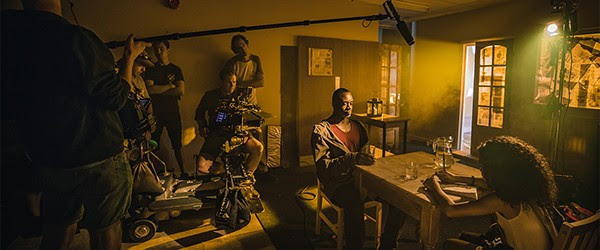 A man and woman sit at a kitchen table with eerie yellow light coming in from outside. A film crew record them