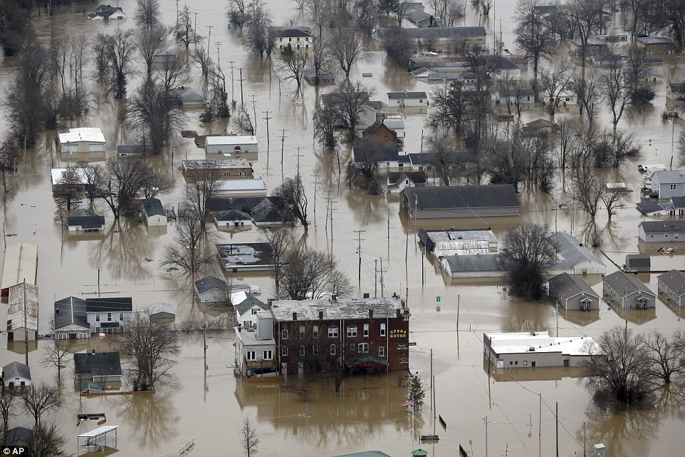 Floodwater has swamped settlements and forced widespread evacuations in a crisis that had claimed more than 20 lives. Pictured, homes and businesses in Pacific, Missouri