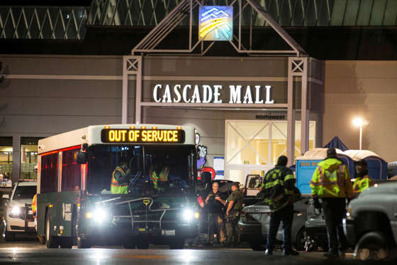 Emergency personnel stand in front of an entrance to the Cascade Mall