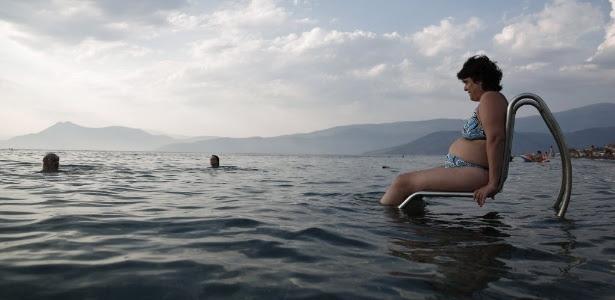 """Matoula Kastrioti, de 46 anos e que tem esclerose múltipla, aprecia a praia sentada no """"Seatrac"""" - dispositivo movido a energia solar que permite às pessoas com deficiência entrar e sair do mar de forma autônoma - em uma praia no oeste de Atenas, Grécia. A foto é de 2013"""
