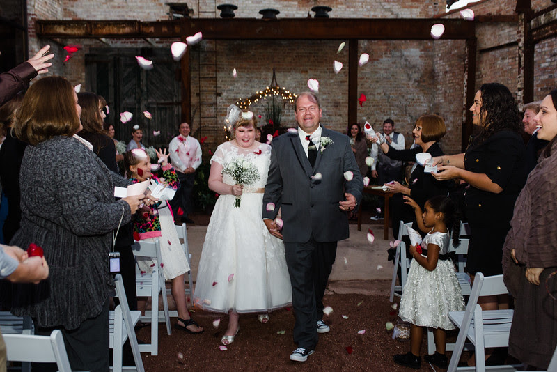 Guests throw rose petals at Audrey and Matt as they exit their ceremony for this chic Wedding Ceremony at Blumen Gardens in Sycamore Illinois for a late summer wedding.